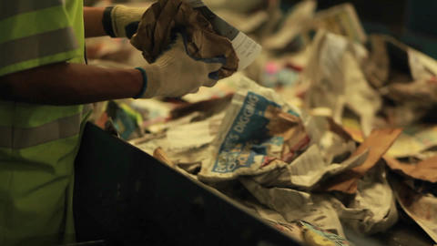 A worker sorts paper products at a recycling cente Footage