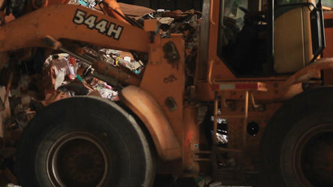 Skip loader shovels recycling at a factory Stock Video Footage