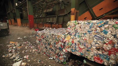 A skip loader moves aluminum cans at a recycling c Footage