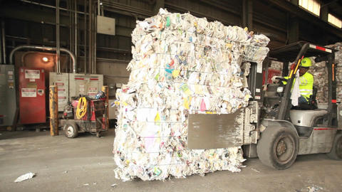Step motion of a skip loader moves aluminum cans a Footage