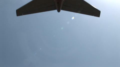 A jet airplane passes directly overhead Footage