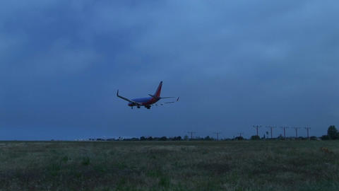 A jet airplane lands on an airport runway against darkened skies Footage