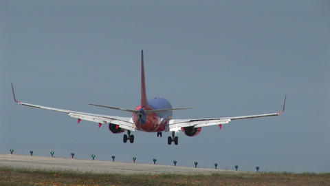 A Southwest jet airplane lands on an airport runway Footage