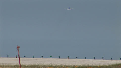 A jet airplane lands as another jet takes off at an airport Footage