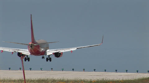 A jet airplane lands as another jet takes off at an airport Stock Video Footage