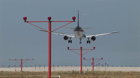 A jet airplane lands on an airport runway Stock Video Footage