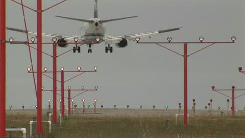 An airplane landing on a runway through lights and guidance equipment beams Footage