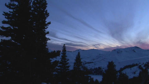 Panning-shot of snowy mountains to a man tending a... Stock Video Footage