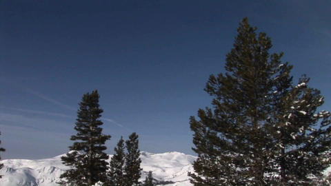 Panning-shot from snowy mountains to a camper digging... Stock Video Footage