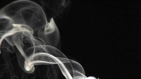 Close-up of incense smoke rising against a black background Footage
