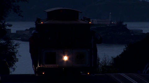 A San Francisco cable car rises over a hill at night Footage