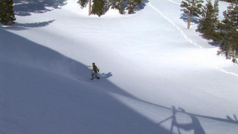 Following shot of a snowboarder as he makes a thrilling jump from a cliff and makes a good landing Footage