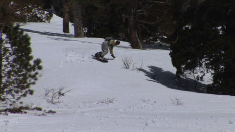 Following shot of a snowboarder racing down a hill Footage