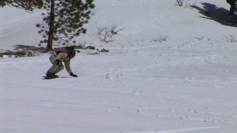 Following shot of a snowboarder racing down a hill Stock Video Footage