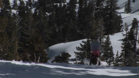 Pan-down shot of hikers moving up a steep and snowy mountain slope Footage