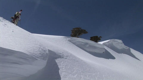 Long-shot of hikers ascending a snowy mountain with snowboards on their backs Footage
