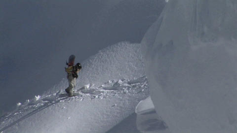 Hikers with snowboards climb a snowy mountain Stock Video Footage
