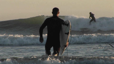 A surfer wades into the ocean Stock Video Footage
