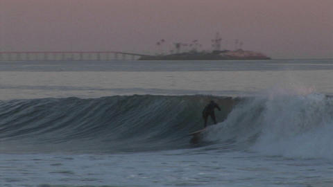 A surfer rides an ocean wave along the California coast Footage
