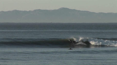 Surfers ride the ocean waves along the coast of Ca Stock Video Footage
