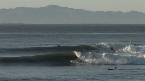 Surfers ride the ocean waves along the coast of Ca Footage