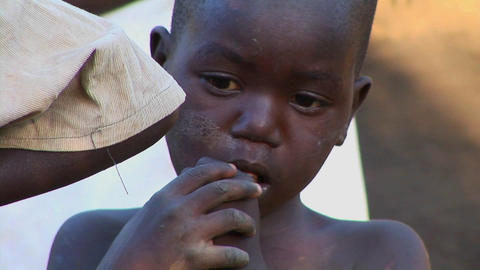 A young orphan child touches his fingers to his mouth in... Stock Video Footage