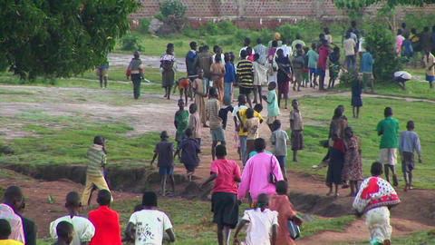 Long-shot of African children run down a country road Stock Video Footage
