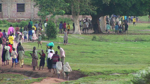 Long-shot of villagers walking on a country path in... Stock Video Footage