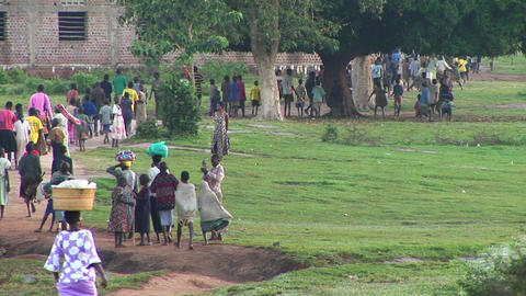 Long-shot of villagers walking on a country path in Uganda, Africa Footage