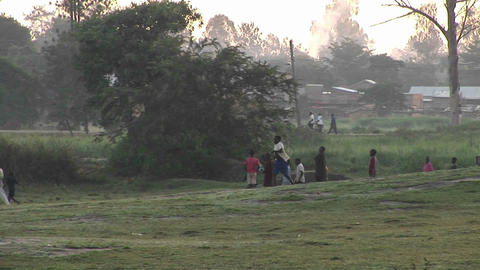 A boy runs near a village in Uganda Stock Video Footage