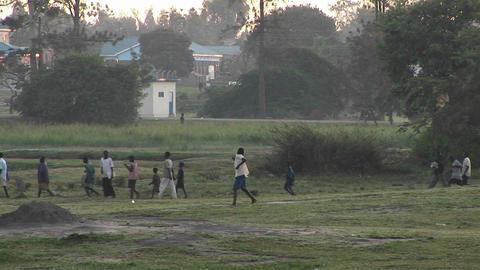 A boy runs near a village in Uganda Stock Video Footage