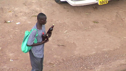 A man carries beer bottles through traffic in Kampala,... Stock Video Footage