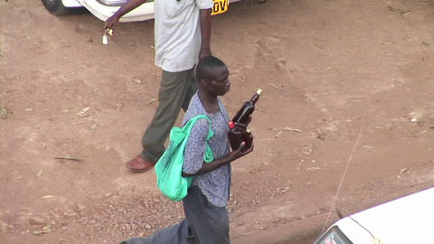 A man carries beer bottles through traffic in Kampala, Uganda Footage