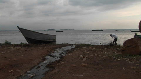 Medium shot of a fisherman working on the shores of Lake Victoria, Uganda near boats Footage