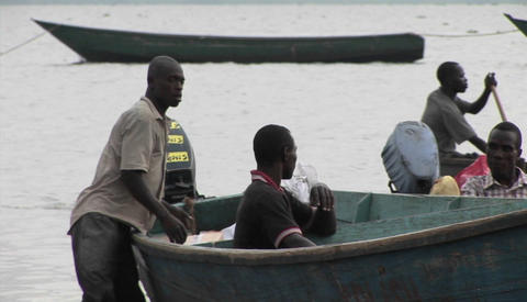 Medium-shot of fishermen and their boats along the shore of Lake Victoria, Uganda Footage
