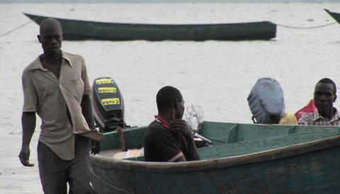 Medium-shot of fishermen and their boats along the shore... Stock Video Footage