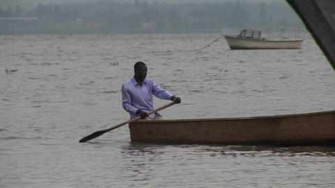 Pan-right of a the oarsman of a fishing boat on Lake... Stock Video Footage