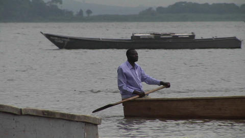 Pan-right of a the oarsman of a fishing boat on Lake Victoria, Uganda Footage