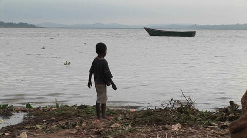 Medium-shot of a young boy playing on the shore of Lake... Stock Video Footage