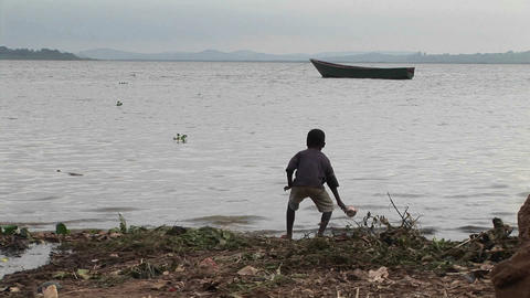 Medium-shot of a young boy playing on the shore of Lake Victoria, Uganda Footage