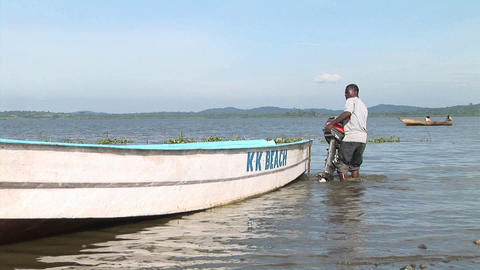 Zoom-in of a young Ugandan man attaching an outboard motor to a fishing skiff Live Action