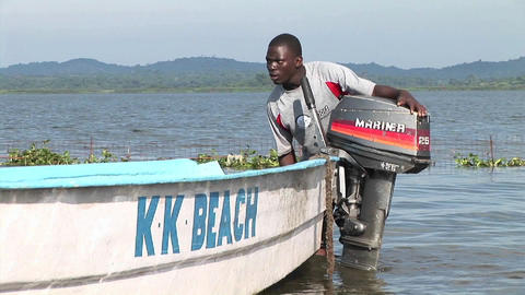 Zoom-in of a young Ugandan man attaching an outboard... Stock Video Footage