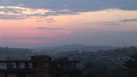 Zoom-out of a flock of birds flying over Kampala, Uganda Footage