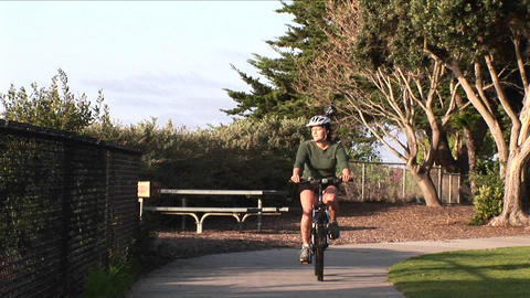 Following shot of a woman riding her bicycle on a path near the ocean Footage