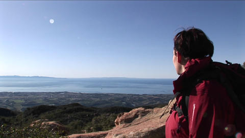 Medium shot of a woman hiking up a hill and turning to... Stock Video Footage