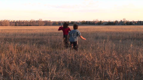 Medium shot of a boy and girl run freely out into an open field Footage