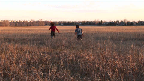 Medium shot of a boy and girl run freely out into an open... Stock Video Footage