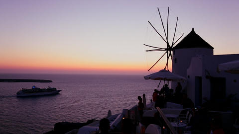 A cruise ship passes windmills at dusk or sunset o Footage