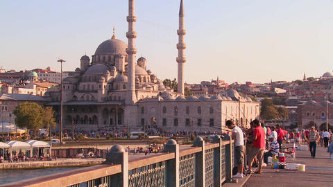 Fishermen stand on a bridge in front of the mosque Stock Video Footage