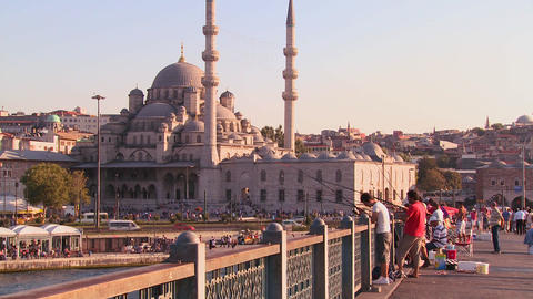 Fishermen stand on a bridge in front of the mosque Footage